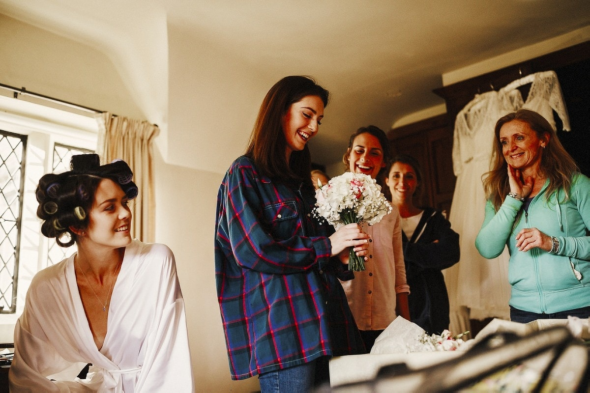 Bridesmaids looking at bride's bouquet