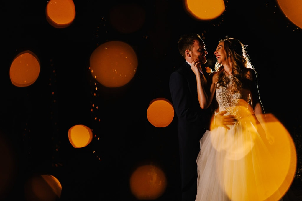 Nighttime portrait of Bride and Groom shot through fairy lights with yellow bokeh