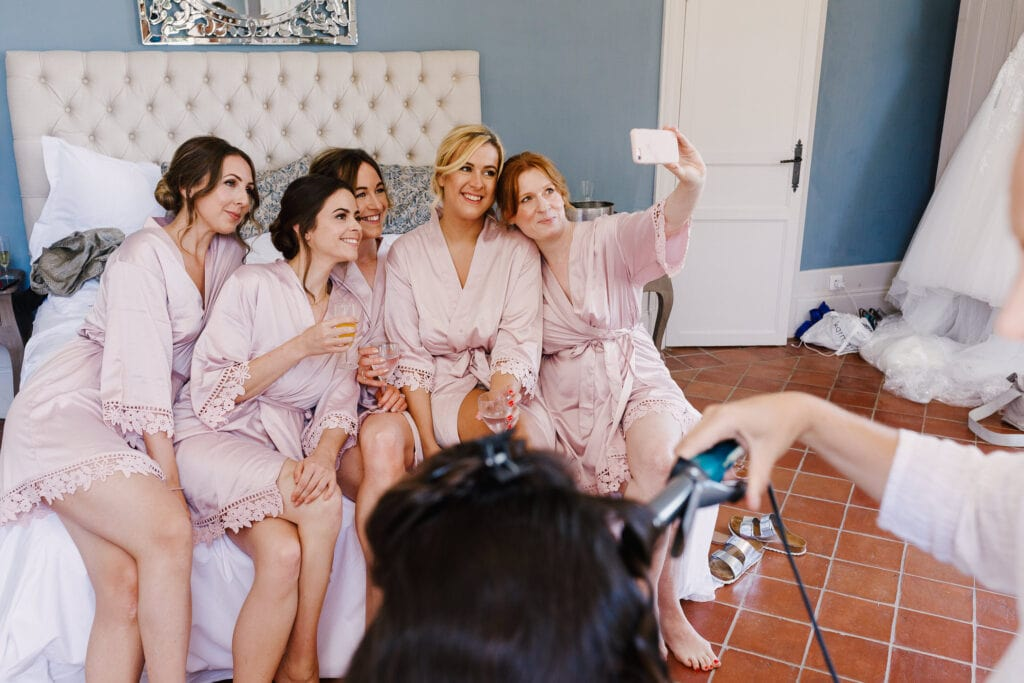 Bridesmaids in pink gowns in bridal suite at Chateau Soulac taking a selfie