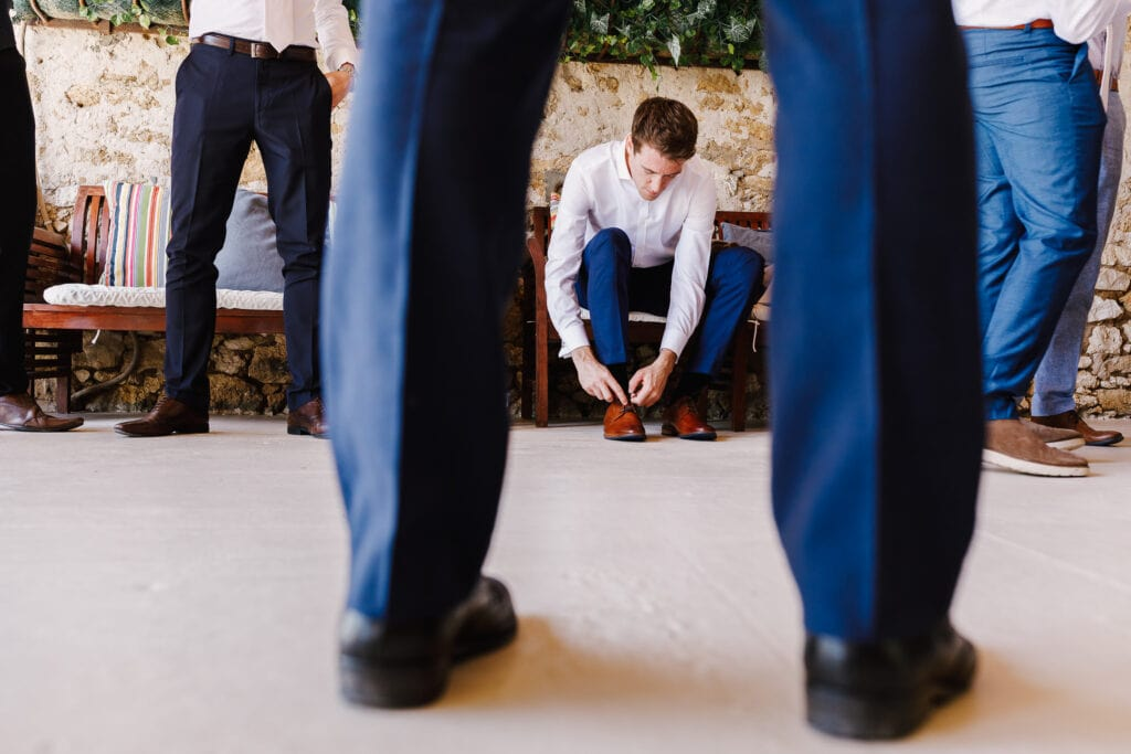 Groom putting on shoes in barn at Chateau Soulac