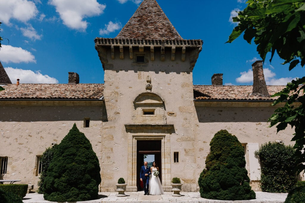 Bride and father coming out of Chateau Soulac