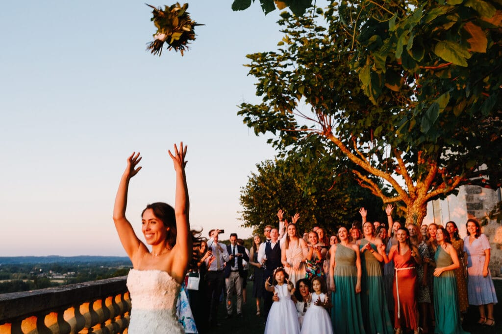 Bride tossing bouqet on terrace at Chateau Soulac