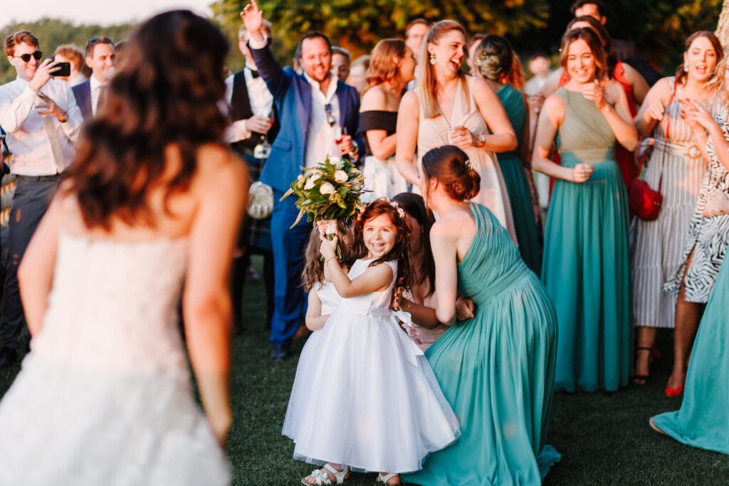 Flower girl catches bouqet on terrace at Chateau Soulac